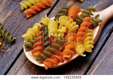 Colorful pasta in a wooden spoon on table
