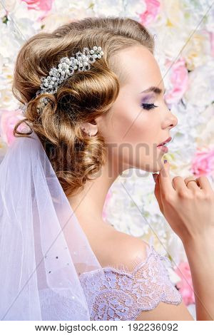 Close-up portrait of a beautiful bride woman. Wedding make-up and hairstyle. Jewellery.