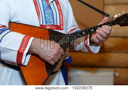 Balalaika wooden in the hands of the musician. Slavic Russian national costume with embroidery. Folk musical art of the rural traditional.