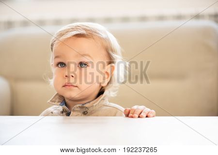 Portrait Of Little Boy With Blue Eyes Looking Up.