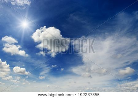 Bright sun and white clouds on the background of an epic dark blue sky.