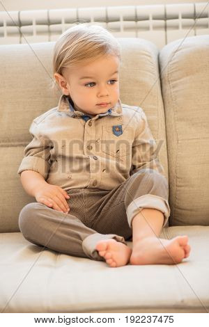 Nicely Dressed Little Boy With Blue Eyes Sitting On The Sofa.