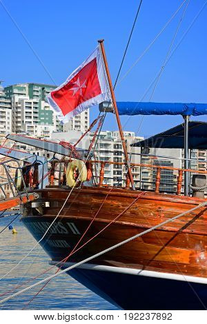 SLIEMA, MALTA - MARCH 30, 2017 - Stern of a wooden yacht moored along the quayside with a Maltese flag Sliema Malta Europe, March 30, 2017.