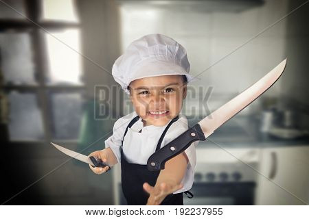 Funny portrait of a four years girl dressed as a cook throwing a knife