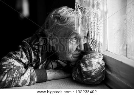 An elderly woman looks wistfully out the window. Black-and-white photo.