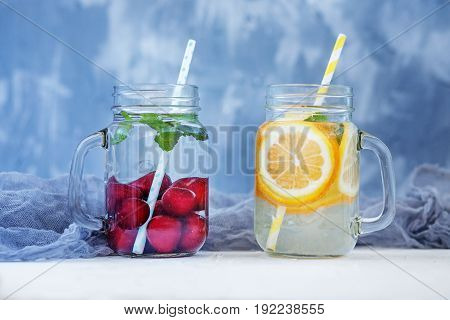 Refreshing fruit water in a glass jar. Lemon orange and mint and cherry. The concept is summer diet vegetarian fitness healthy eating and lifestyle.