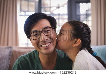 Daughter kissing father on cheeks in living room at home
