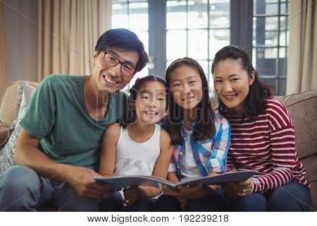 Portrait of family with photo album together in living room at home