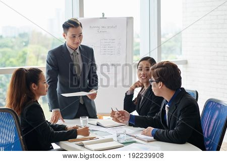 Group of talented managers gathered together in spacious boardroom and discussing faced issue, panoramic window on background