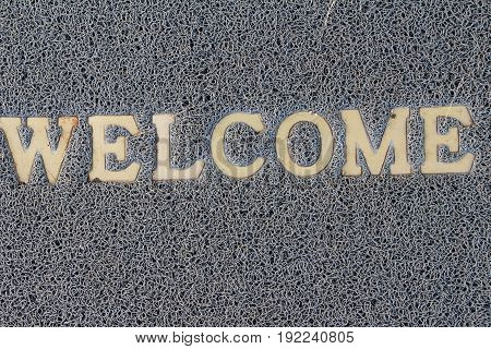 Welcome door mat on background and texture
