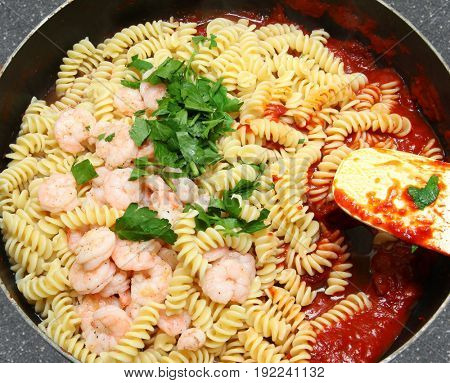 Shrimp and Fusilli Pasta with parsley and tomato paste in pan.