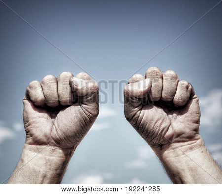 Two dirty male hands clenched in fist against the sky