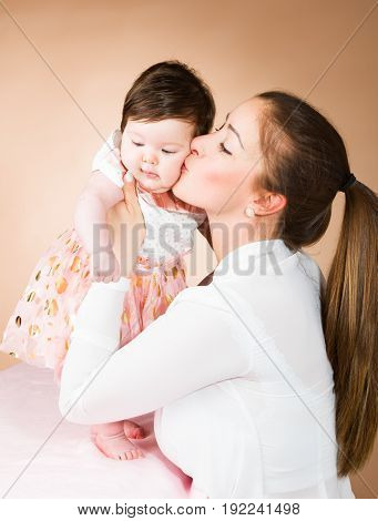 Happy mother and six months old baby girl.