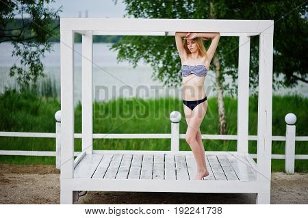 Portrait Of A Beautiful Girl Model Standing And Posing On A White Wooden Gazebo Next To The Lake.