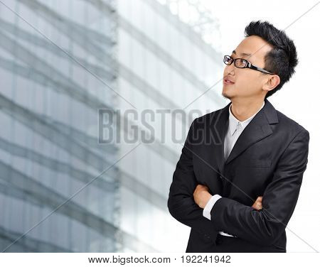 Young Asian man looking outside through windows