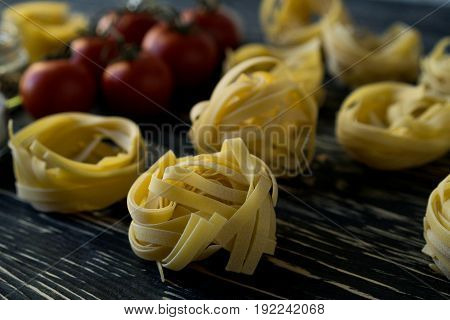 Pasta ingridients and spice on wooden background.