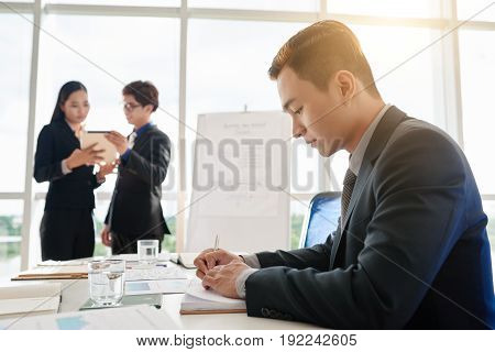 Profile view of handsome young manager with stylish haircut focused on work while sitting at table in spacious boardroom, colleagues with digital tablet standing at some distance