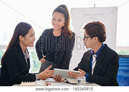 Young Asian business people discussing data presented on screen of digital tablet during working meeting in modern boardroom with panoramic windows