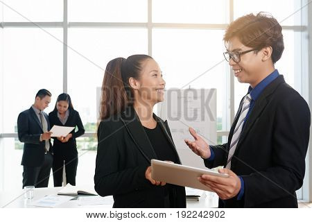 Profile view of cheerful young coworkers working on their joint project with help of digital tablet while having informal meeting in spacious boardroom