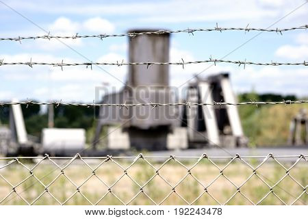 The close-up of a fence with barbed wire in front of a factory site with large factory plants.