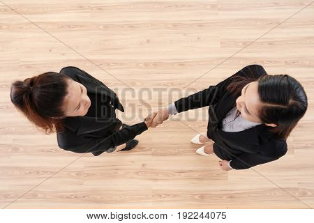 Confident businesswomen in formal wear shaking hands while standing in spacious office lobby, directly above view