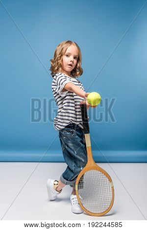 Adorable Little Girl Standing With Tennis Raquet And Ball While Looking At Camera