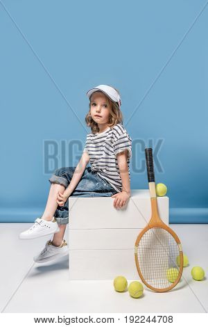 beautiful little girl sitting on white boxes with tennis raquet and balls