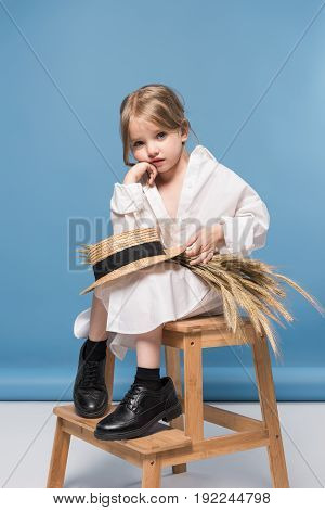 Pensive Adorable Little Girl In White Dress Holding Wheat Ears And Straw Boater, Studio Shot On Blue