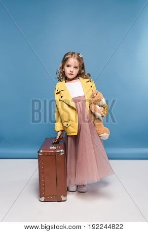 Cute Pensive Little Girl Holding Teddy Bear And Suitcase In Studio