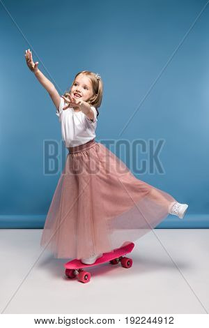 Cute Smiling Girl In Pink Skirt Standing On Skateboard And Having Fun
