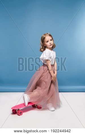 Cute Little Girl In Pink Skirt Posing With Skateboard And Looking Away