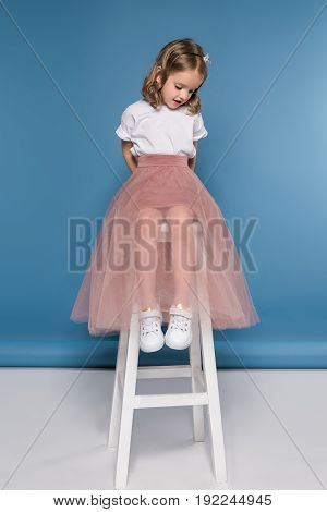 Beautiful Girl In Pink Skirt Sitting On Ladder And Looking Down