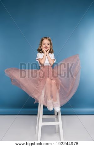 Adorable Little Girl In Pink Skirt Sitting On Ladder And Looking At Camera