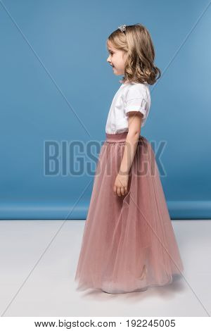 Side View Of Cute Little Girl In Pink Skirt Smiling And Looking Away