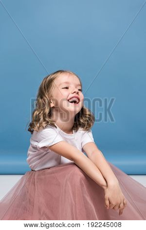 Portrait Of Adorable Little Girl In Pink Skirt Sitting On Floor And Laughing