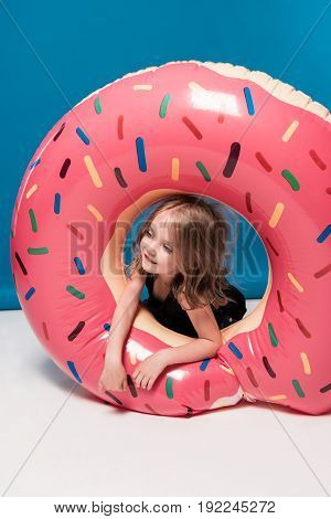 Adorable Little Girl Playing With Swimming Tube In Form Of Doughnut