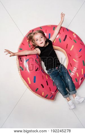 Little Girl Resting On Swimming Tube In Shape Of Doughnut
