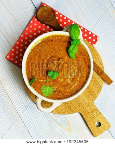 Homemade Fresh Squash Caviar with Basil Leafs in White Bowl closeup on Wooden Board with Napkin and Wooden Spoon. Top View