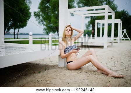 Portrait Of A Gorgeous Young Girl In Bikini Sitting Next To The Gasebo On Sand And Posing.