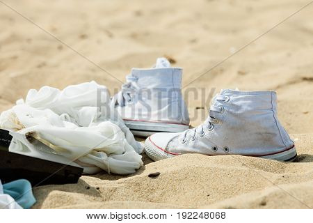 Pefect footwear for summer concept. Pair of white sneakers on sandy beach
