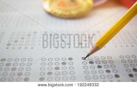 yellow pencil on exam answer sheet with medals blur background education test and winner concept