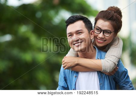 Portrait of young man carrying pretty Asian woman on back, giving piggyback ride on date, having fun