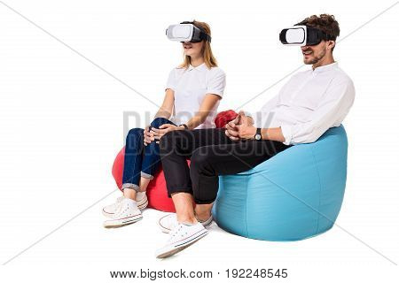 Excited young couple experiencing virtual reality seated on beanbags isolated on white background. A young couple dressed in jeans, white t-shirts and sneakers