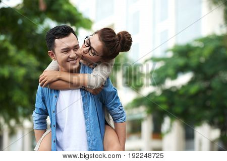 Portrait of young Asian couple on date: pretty girl riding piggyback and kissing boyfriend on cheek enjoying date outdoors
