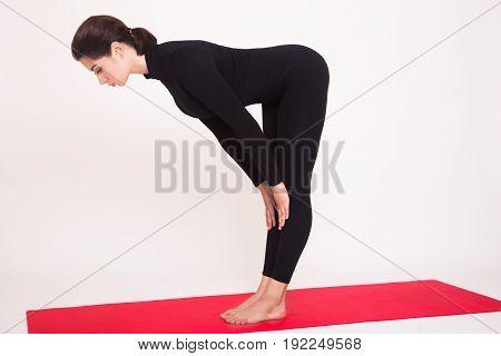 Beautiful athletic girl in black suit doing yoga asanas. Isolated on white background