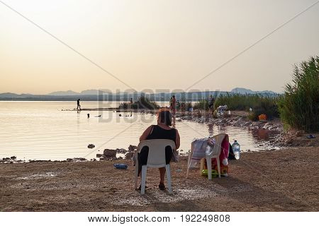 Torrevieja, Spain - June 26, 2016: Different people, men, women and children are taking procedures on a salt lake with pink water. At lake Las Salinas