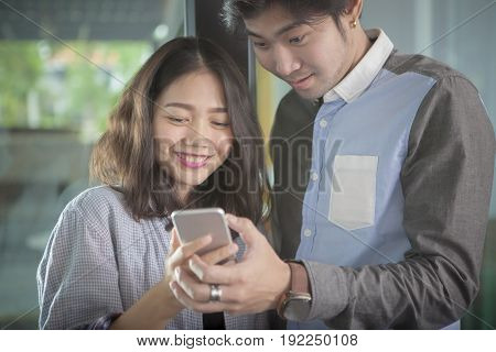 asian younger man and woman looking to smart phone screen toothy smiling face happiness emotion