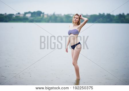 Portrait Of A Beautiful Bikini Model Standing And Posing In The Water.