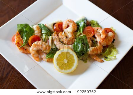 Shrimp salad on a white plate on a brown table. Shrimp lemon salad leaves.