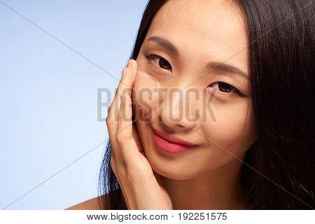 Beauty, health, girl on blue background, face cream, asian, portrait.
